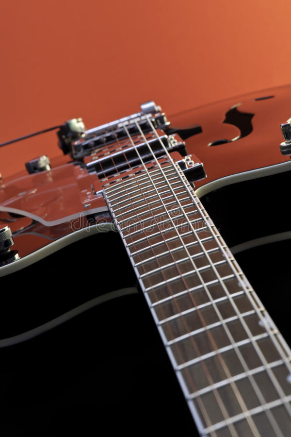 Hollow Body Guitar. Macro shot of a hollow body Guitar. The Guitar was lit from a red background and speedlite. No logos present. Contrast has been added to give royalty free stock images