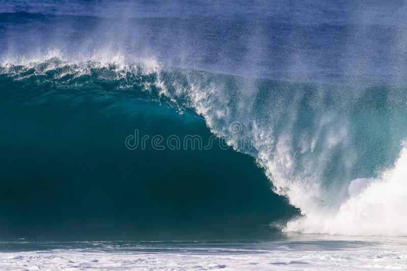 Hollow Crashing Wave. Clean blue ocean wave of size,energy and power surges or crashes onto the shallow sandbank royalty free stock images
