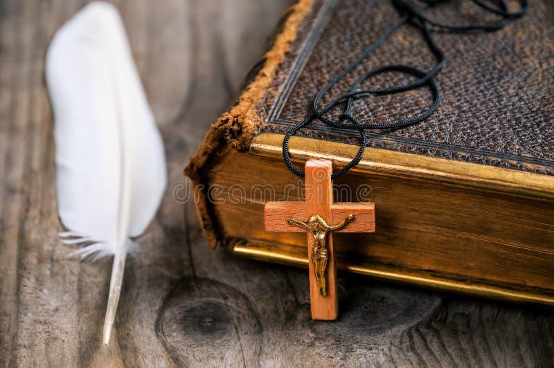 Holly Bible, kruis en veer stock fotografie