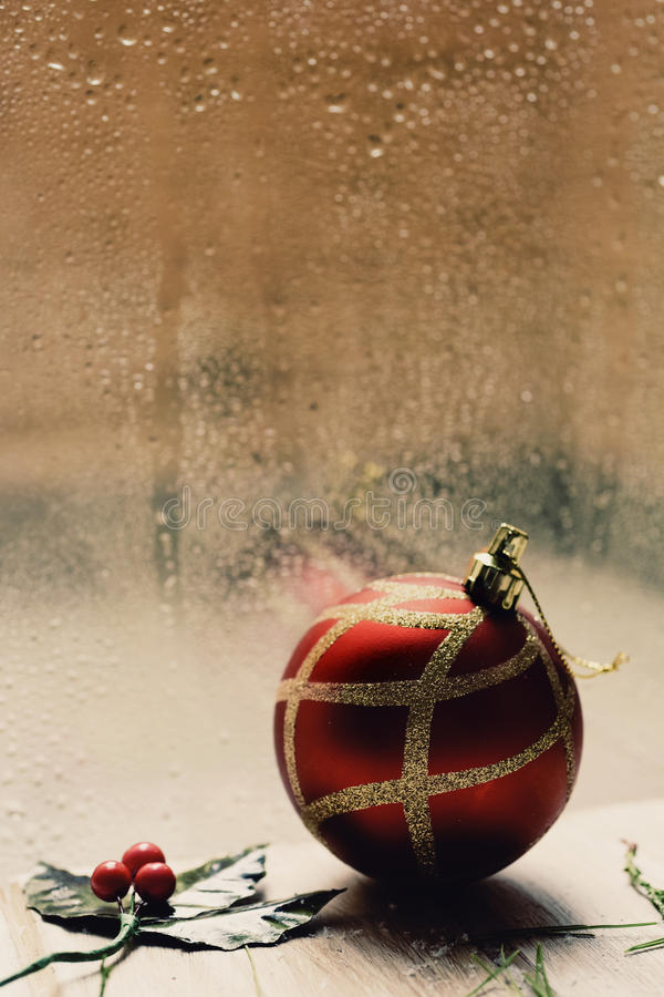 Holly and christmas ball in a rainy day. A twig of holly and a red and golden christmas ball on a rustic wooden table in front of a window splattered with stock image