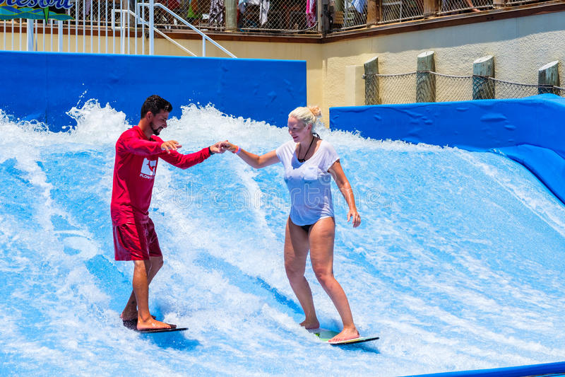 Hollywood Beach Florida. Hollywood Beach, Florida - July 6, 2017: A visitor enjoying the wave riding flowrider attraction at the Margaritaville Resort, a popular stock photo