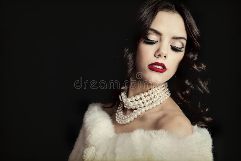 Hollywood Glam. Classic Hollywood starlet in white fur stole, classic pearl necklace, and bright red lipstick. Shot on black background stock images