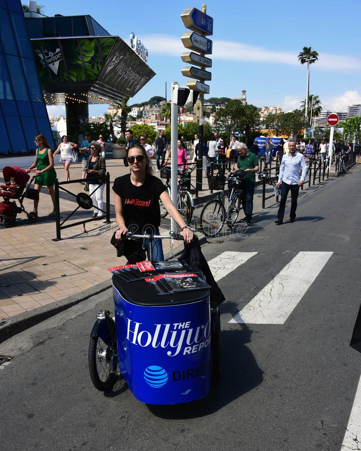 Hollywood Reporter cyclist at Cannes Film Festival. Cannes, France – May 11, 2018: An unidentified woman cycles a bike filled with Hollywood Reporter royalty free stock photos