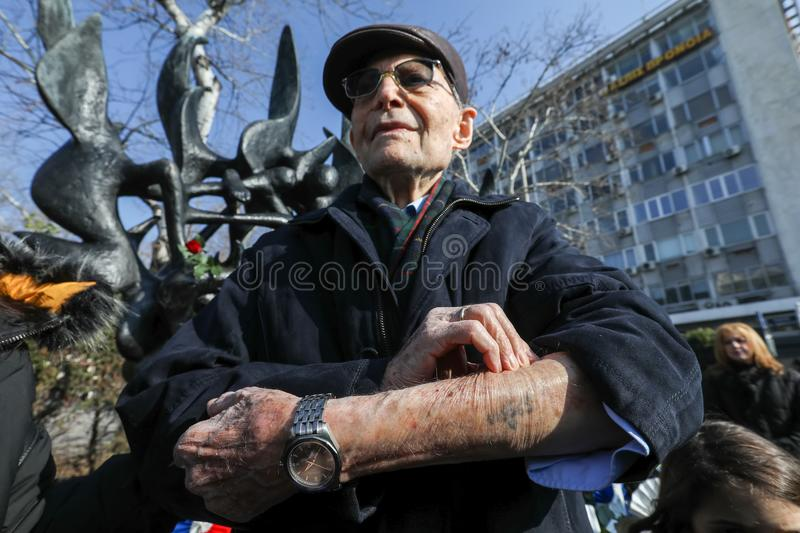 Holocaust survivor Heinz Kounio shows his tattooed serial number royalty free stock image