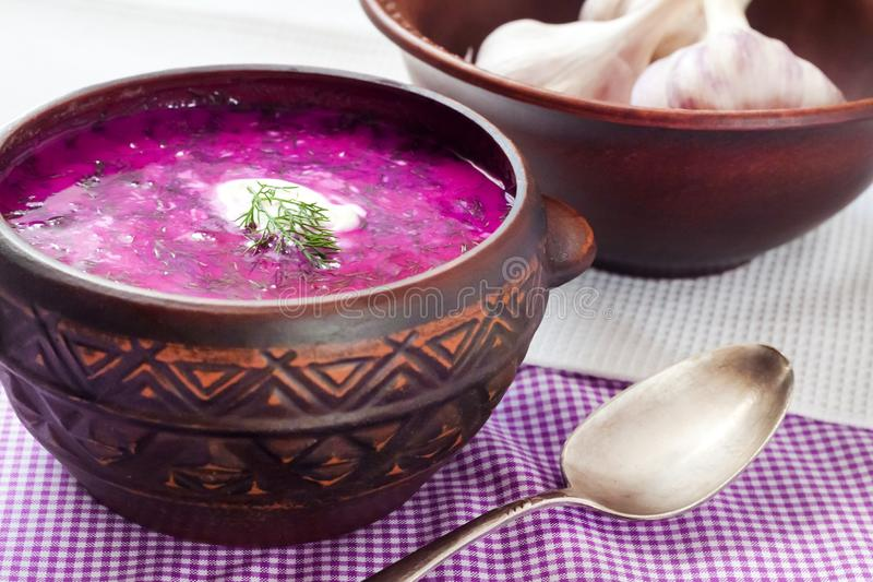 Holodnik - traditional Lithuanian Russian, Ukrainian, Belorussian, Polish cold beetroot soup. With cucumber, boiled eggs and greens in rustic bowl royalty free stock image