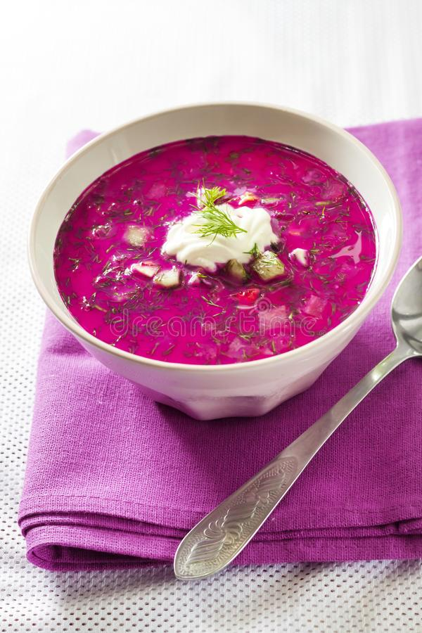 Holodnik - traditional Lithuanian Russian, Ukrainian, Belorussian, Polish cold beetroot soup. With cucumber, boiled eggs and greens in white bowl on purple stock image