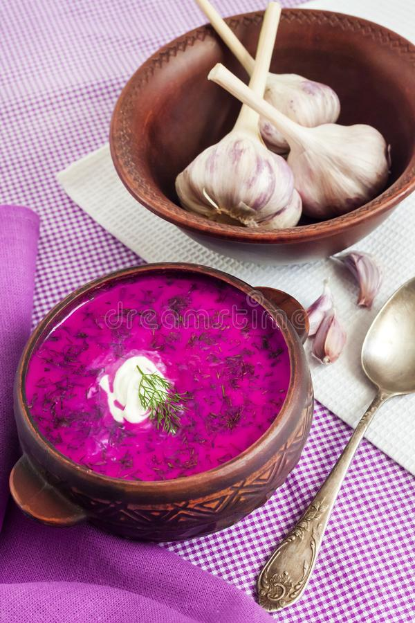 Holodnik - traditional Lithuanian Russian, Ukrainian, Belorussian, Polish cold beetroot soup. With cucumber, boiled eggs and greens in rustic bowl stock images