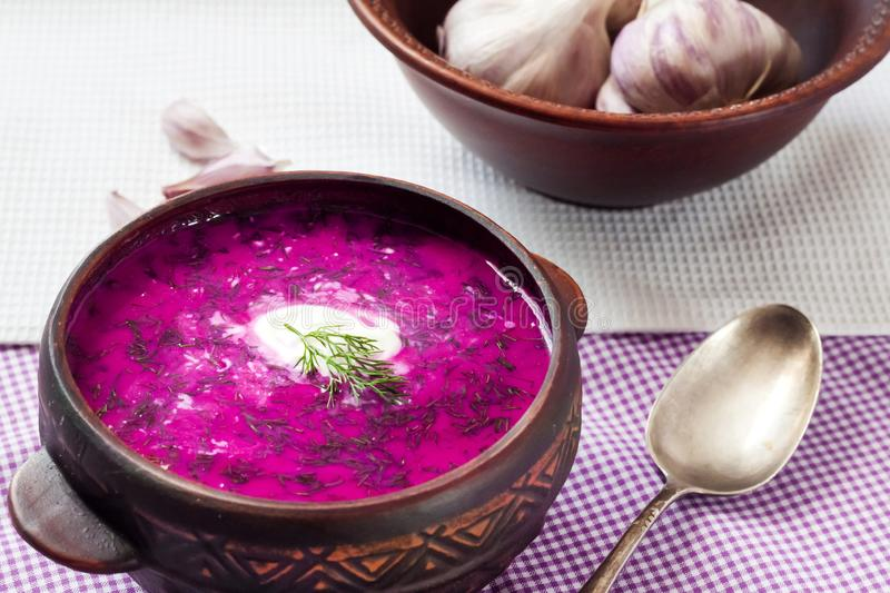 Holodnik - traditional Lithuanian Russian, Ukrainian, Belorussian, Polish cold beetroot soup. With cucumber, boiled eggs and greens in rustic bowl royalty free stock photos