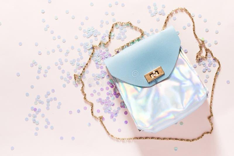 Holografische handtas met gouden kettingshandvat op roze achtergrond Manierconcept in pastelkleuren royalty-vrije stock foto