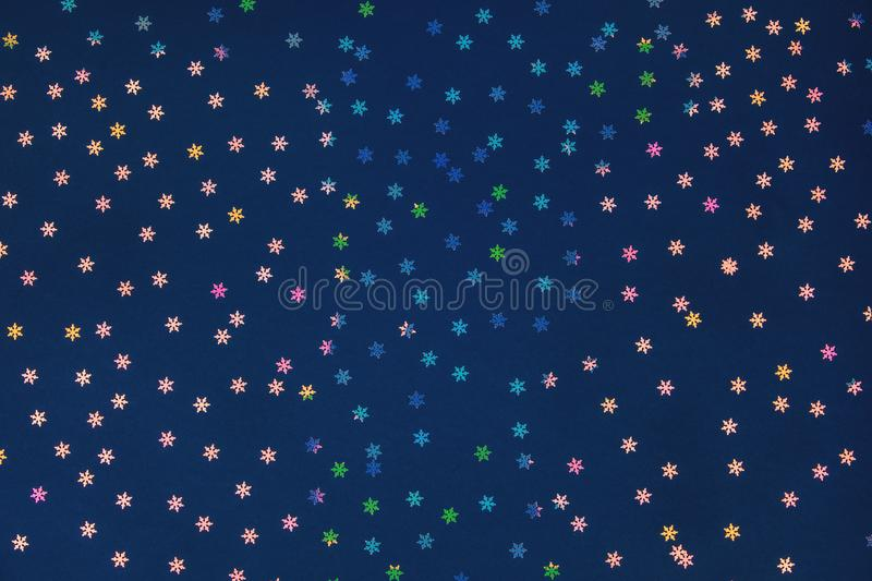 Holographic foil snowflakes confetti sparse on dark blue colored background. Holographic foil snowflakes confetti sparse on dark blue background. Simple royalty free stock images