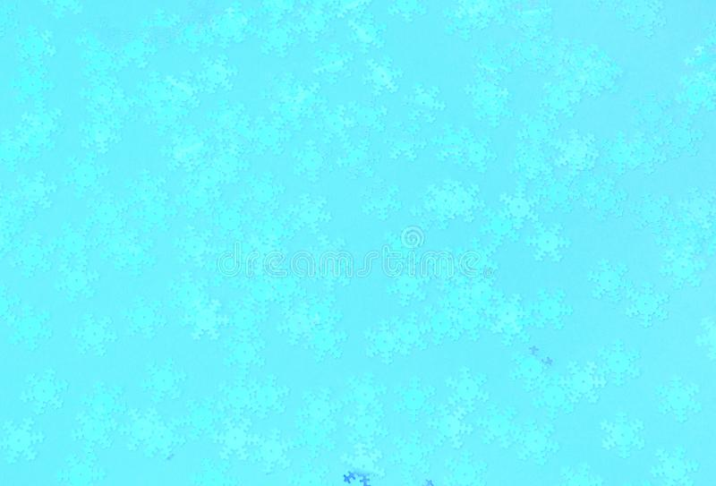 Holographic foil snowflakes confetti sparse on trendy blue color. Holographic foil snowflakes confetti sparse on trendy blue background. Simple holiday concept stock photography