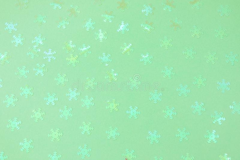 Holographic foil snowflakes confetti sparse on trendy mint colored background. Holographic foil snowflakes confetti sparse on trendy neo mint colored background royalty free stock photo