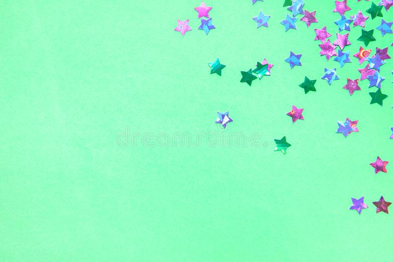 Holographic foil stars confetti sparse on trendy mint colored background. Simple holiday concept. Design template. Corner frame with copy space for text. Top stock photos