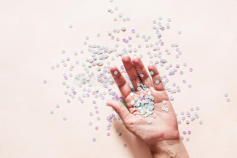 Holographic pastel glitter confetti in female hand on pink background. Creative conceptual backdrop.  royalty free stock photo