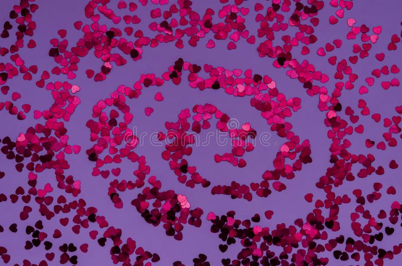Holographic red hearts on trendy purple background spiral shaped . Festive backdrop. Top view stock photos