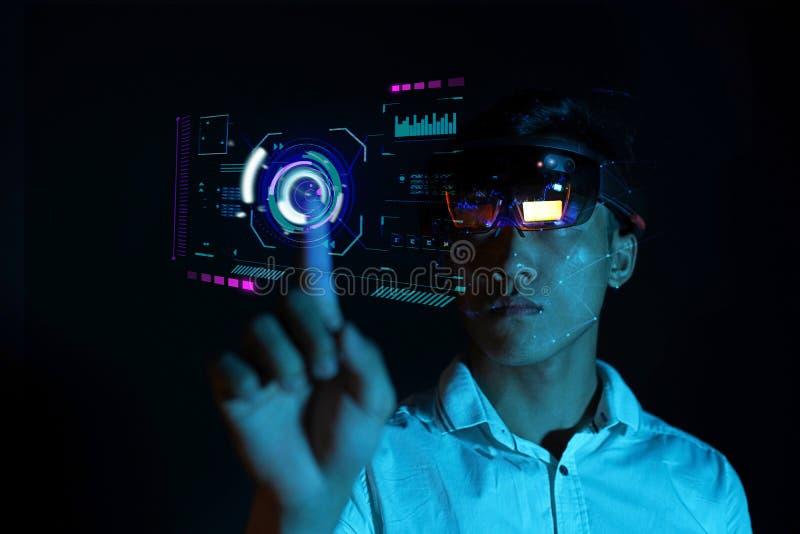 Hololens de los vidrios del vr del intento del hombre de negocios en el cuarto oscuro | Experiencia asiática joven AR del muchach foto de archivo