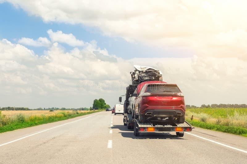 Holowniczej ciężarówki przyczepa na autostradzie niesie trzy uszkadzał samochody sprzedających na asekuracyjnych samochodowych au zdjęcie stock