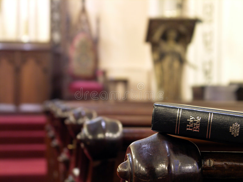 Holy Bible. Bible resting on the back of a church pew. Shallow DOF with sharp focus on bible stock photos