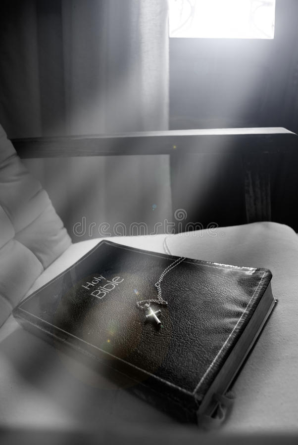The holy Bible. A bible with a cross and a chain, on a chair, under the sunlight entering by a close window. Image on a low sepia grunge background