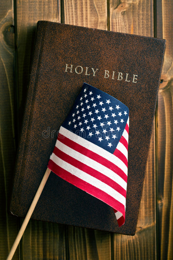 Holy bible with american flag. On wooden background royalty free stock photos