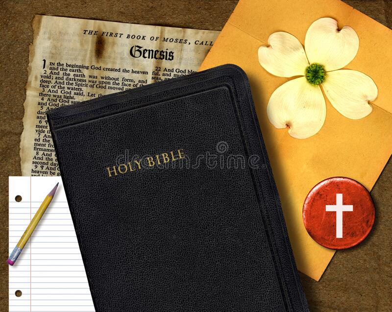 Holy Bible And Book Of Genesis. The Holy Bible next to the book of Genesis, a pen with paper and a flower stock image