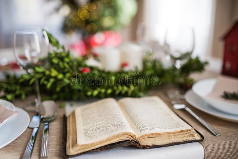 Holy bible book on a table set for a dinner at home at Christmas time. royalty free stock photos