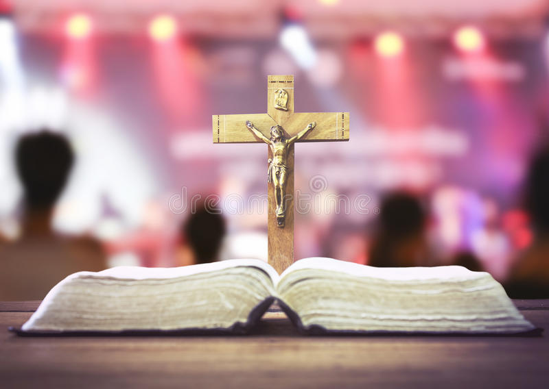 The holy bible and the crucifix over burred concert hall background royalty free stock images