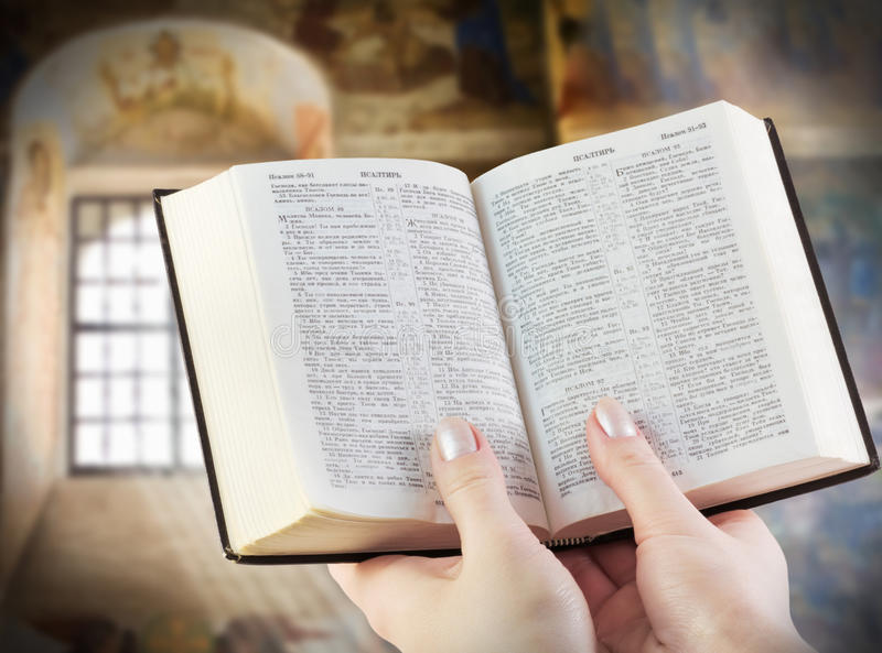 Holy Bible in the Hands. Bible in the hands of the background of old icons stock image