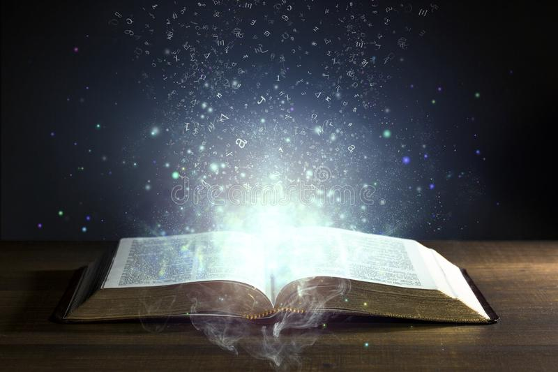 Holy Bible open with glowing lights royalty free stock photo