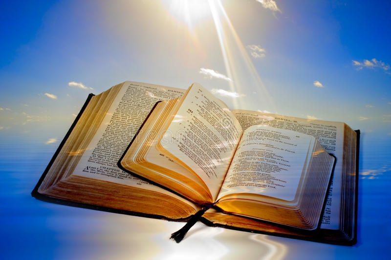 Creation Concept. Holy Bible and Prayer Book, both open with a background of light rays striking page..Concepts of Let There Be Light, Creationism, Glory of the stock photo