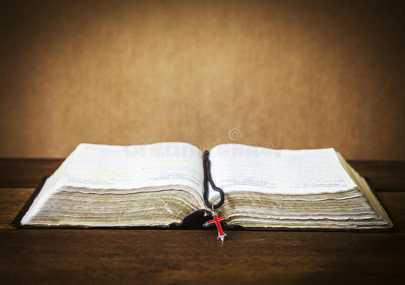 The holy bible and the red cross over on wooden table royalty free stock images