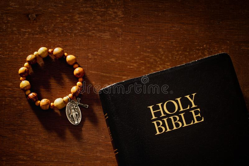 Holy Bible And Rosary Bracelet. On wood in warm light stock image