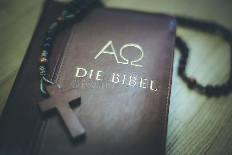 Holy bible and rosary: Christian bible and rosary on a wooden desk. Holy bible and rosary are lying on a wooden desk religion bibel religious catholic church stock photos