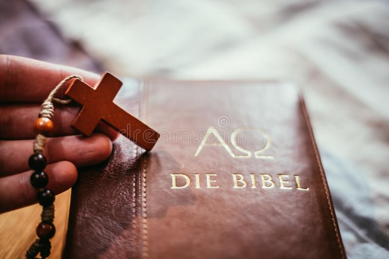 Holy bible and rosary: Christian bible and rosary on a wooden desk. Holy bible and rosary are lying on a wooden desk religion bibel religious catholic church royalty free stock image