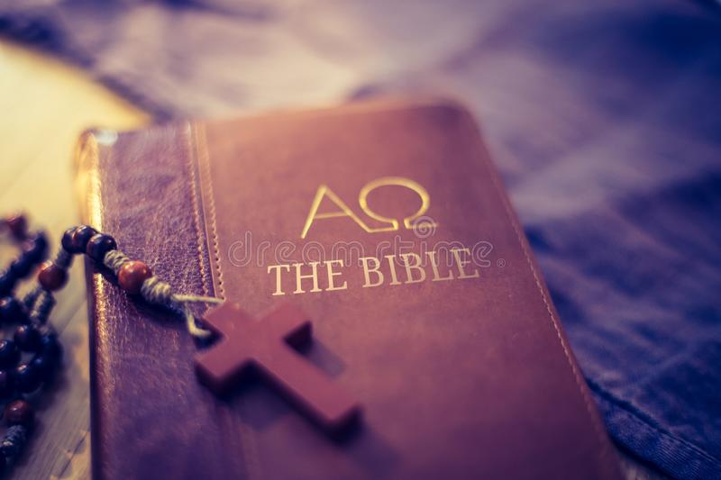Holy bible and rosary: Christian bible and rosary on a wooden desk. Holy bible and rosary are lying on a wooden desk religion bibel religious catholic church stock photo