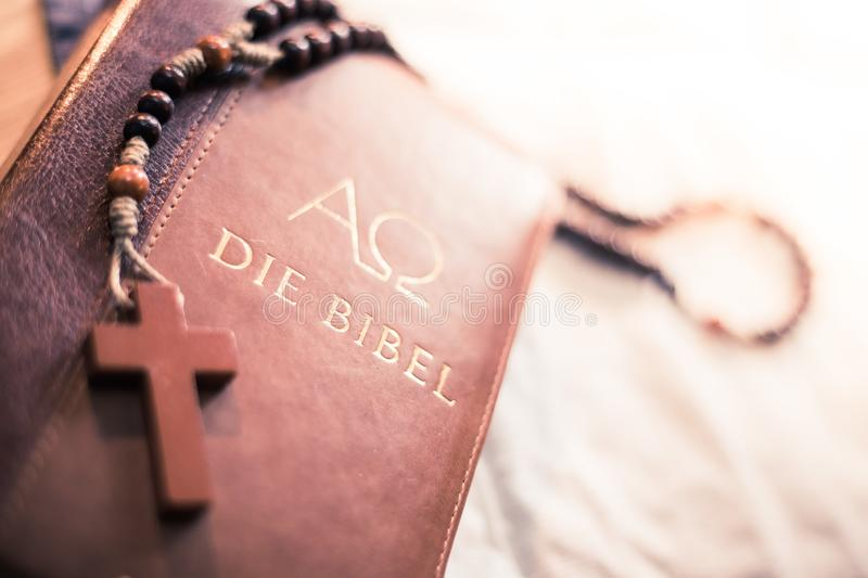 Holy bible and rosary: Christian bible and rosary on a wooden desk. Holy bible and rosary are lying on a wooden desk religion bibel religious catholic church stock image