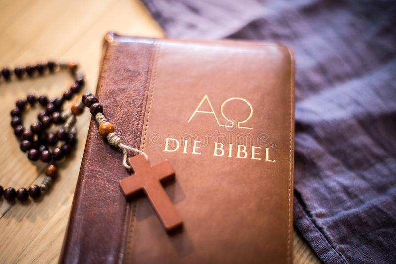 Holy bible and rosary: Christian bible and rosary on a wooden desk. Holy bible and rosary are lying on a wooden desk religion bibel religious catholic church royalty free stock photo