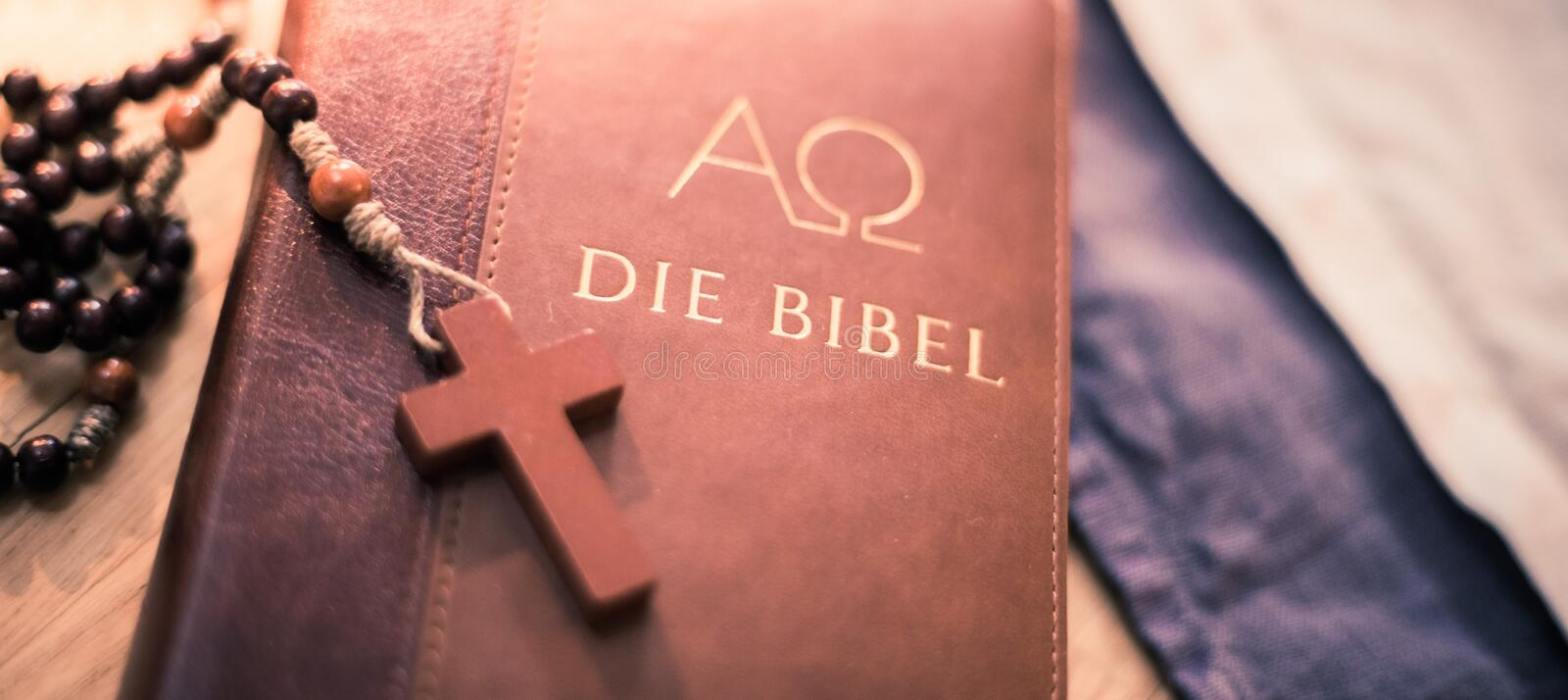 Holy bible and rosary: Christian bible and rosary on a wooden desk. Holy bible and rosary are lying on a wooden desk religion bibel religious catholic church stock images
