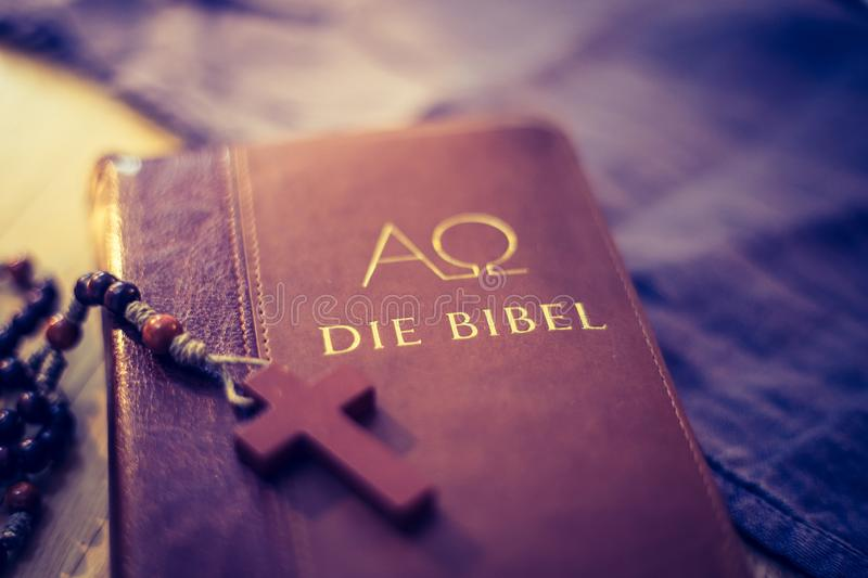 Holy bible and rosary: Christian bible and rosary on a wooden desk. Holy bible and rosary are lying on a wooden desk religion bibel religious catholic church royalty free stock photography