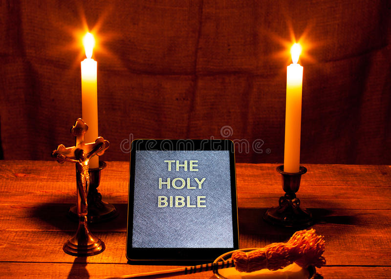 The holy bible in tablet computer. Digital holy bible as a symbol of a new era. Scene from the cross, candles and sprinkler royalty free stock image