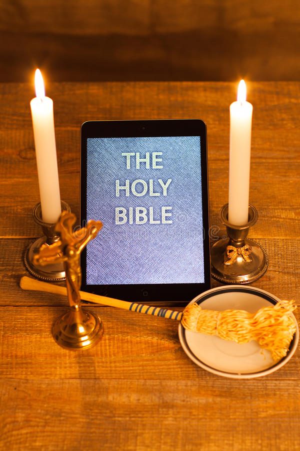 The holy bible in tablet computer. Digital holy bible as a symbol of a new era. Scene from the cross, candles and sprinkler stock images