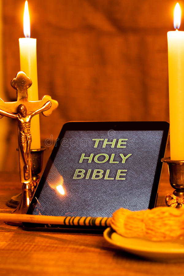 The holy bible in tablet computer. Digital holy bible as a symbol of a new era. Scene from the cross, candles and sprinkler royalty free stock photography
