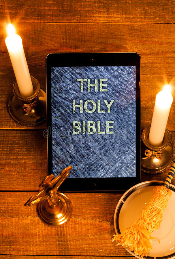 The holy bible in tablet computer. Digital holy bible as a symbol of a new era. Scene from the cross, candles and sprinkler stock photos
