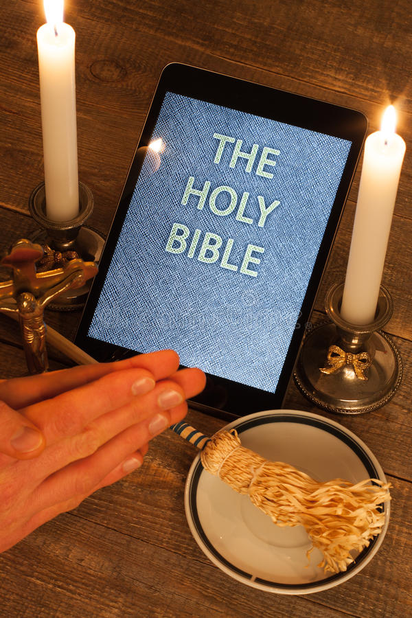 The holy bible in tablet computer. Digital holy bible as a symbol of a new era. Scene from the cross, candles and sprinkler and hands folded in prayer royalty free stock photo