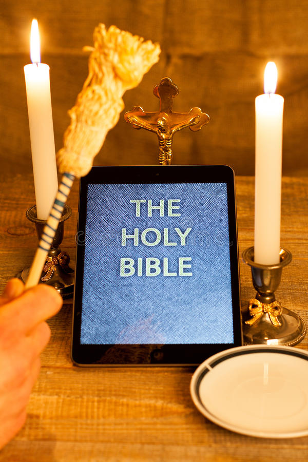 The holy bible in tablet computer. Digital holy bible as a symbol of a new era. Scene from the cross, candles and sprinkler and hands folded in prayer stock images