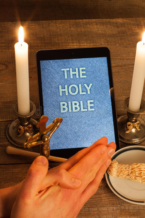 The holy bible in tablet computer. Digital holy bible as a symbol of a new era. Scene from the cross, candles and sprinkler and hands folded in prayer royalty free stock photography