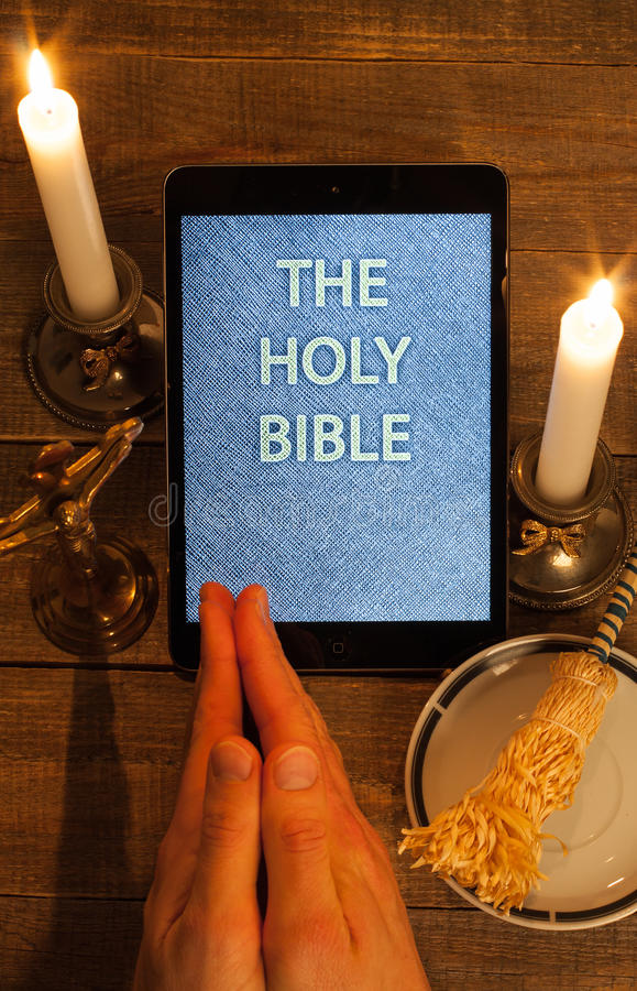 The holy bible in tablet computer. Digital holy bible as a symbol of a new era. Scene from the cross, candles and sprinkler and hands folded in prayer stock image