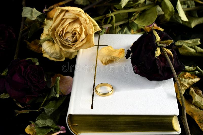 Holy Bible, wedding ring and dry roses. White Holy Bible, one wedding ring and dry roses. Touching conceptual image of marriage, death and `till death do us part royalty free stock photo