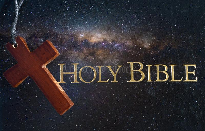 Holy Bible with wooden Cross against a night sky stock image