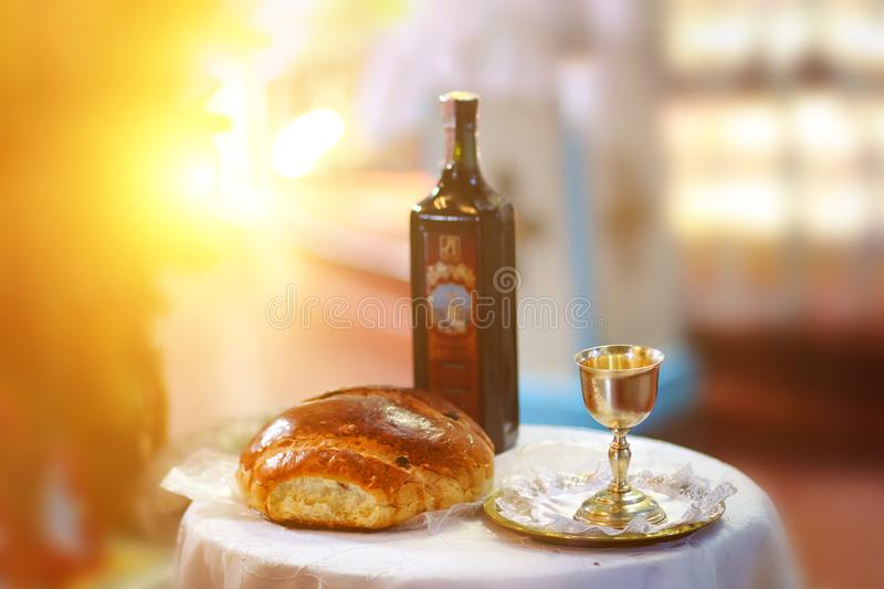 Holy communion on wooden table in church.Taking Communion.Cup of glass with red wine, bread on table.The Feast of Corpus Christi royalty free stock photography